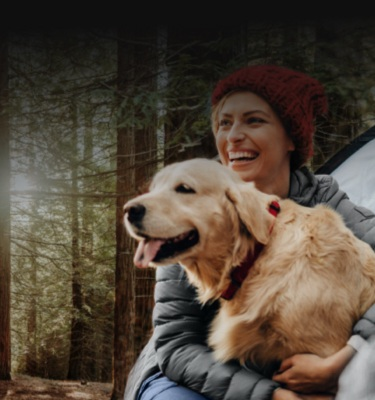 Couple camping in woods with dog